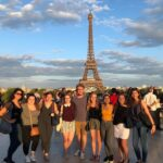 A group of friends standing in front of the Eiffel Tower in Paris, France.