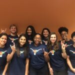 Coworkers together in Flag Bevo shirts throwing up Hook 'Em hand sign