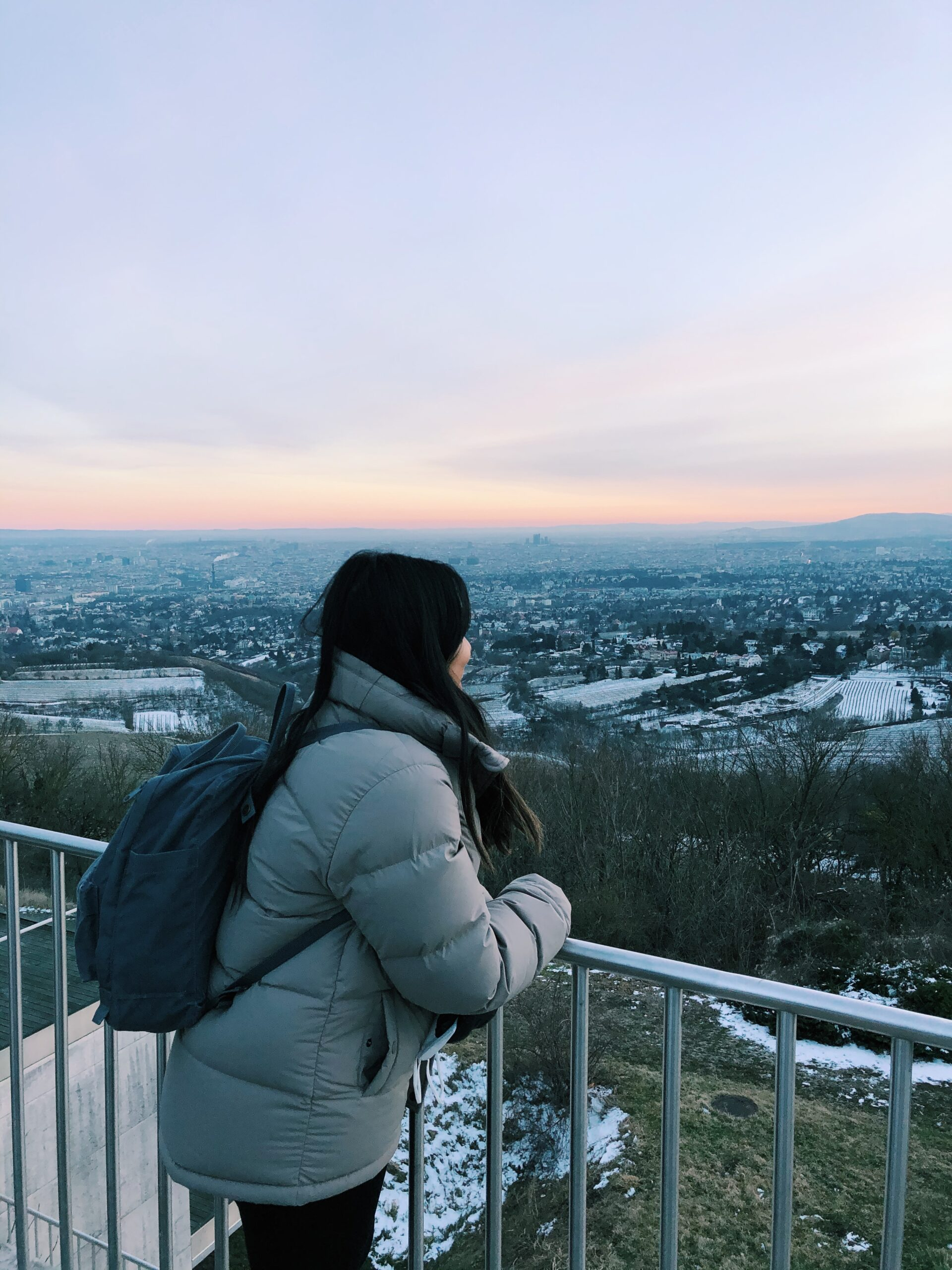 woman stands at railing overlooking city at sunset
