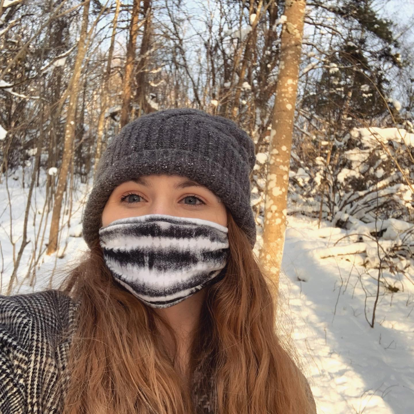 Girl wearing face mask and beanie near snow and trees during daytime