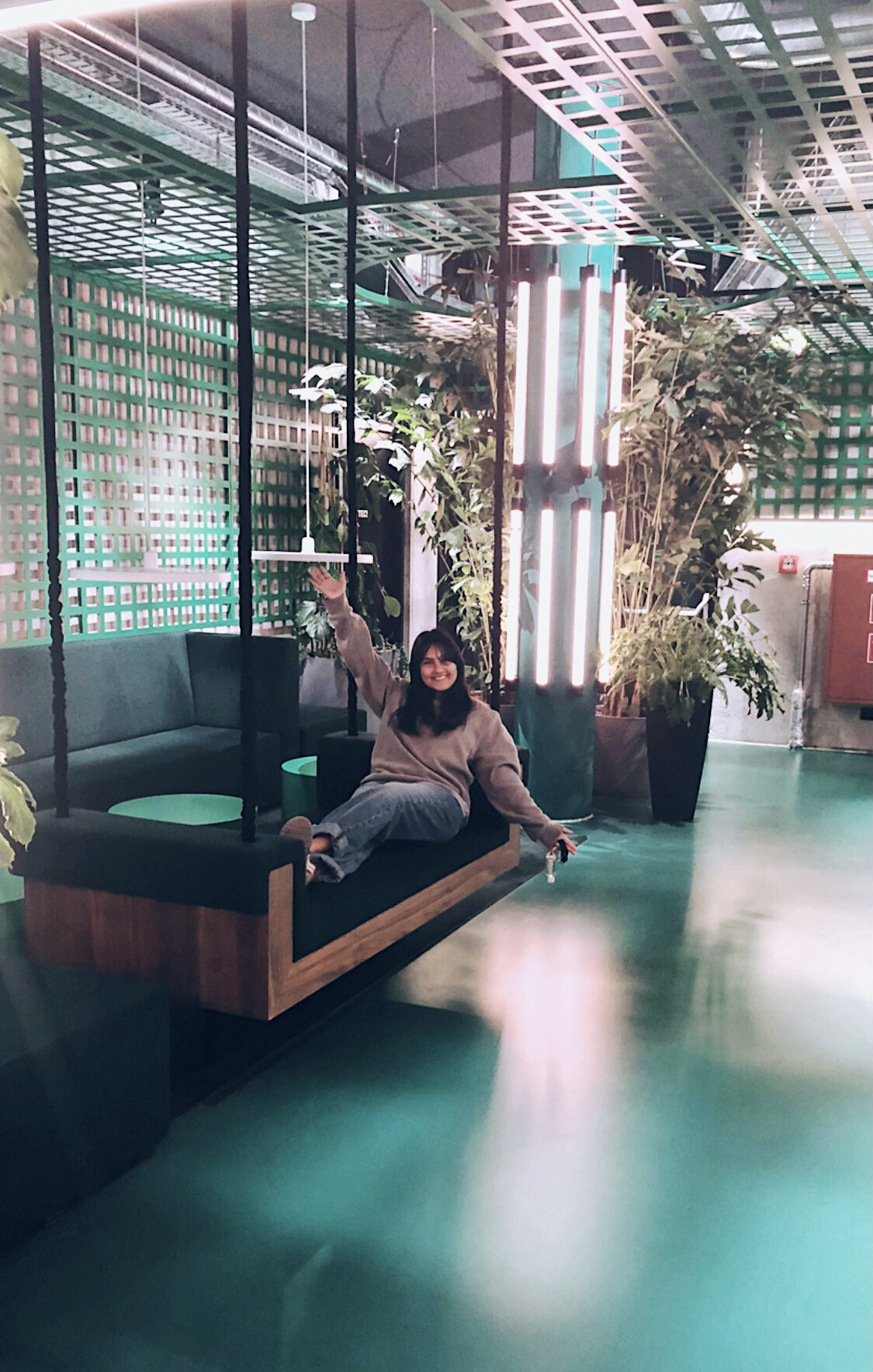woman sits on couch in dimly lit lobby with decorative lighting and plants