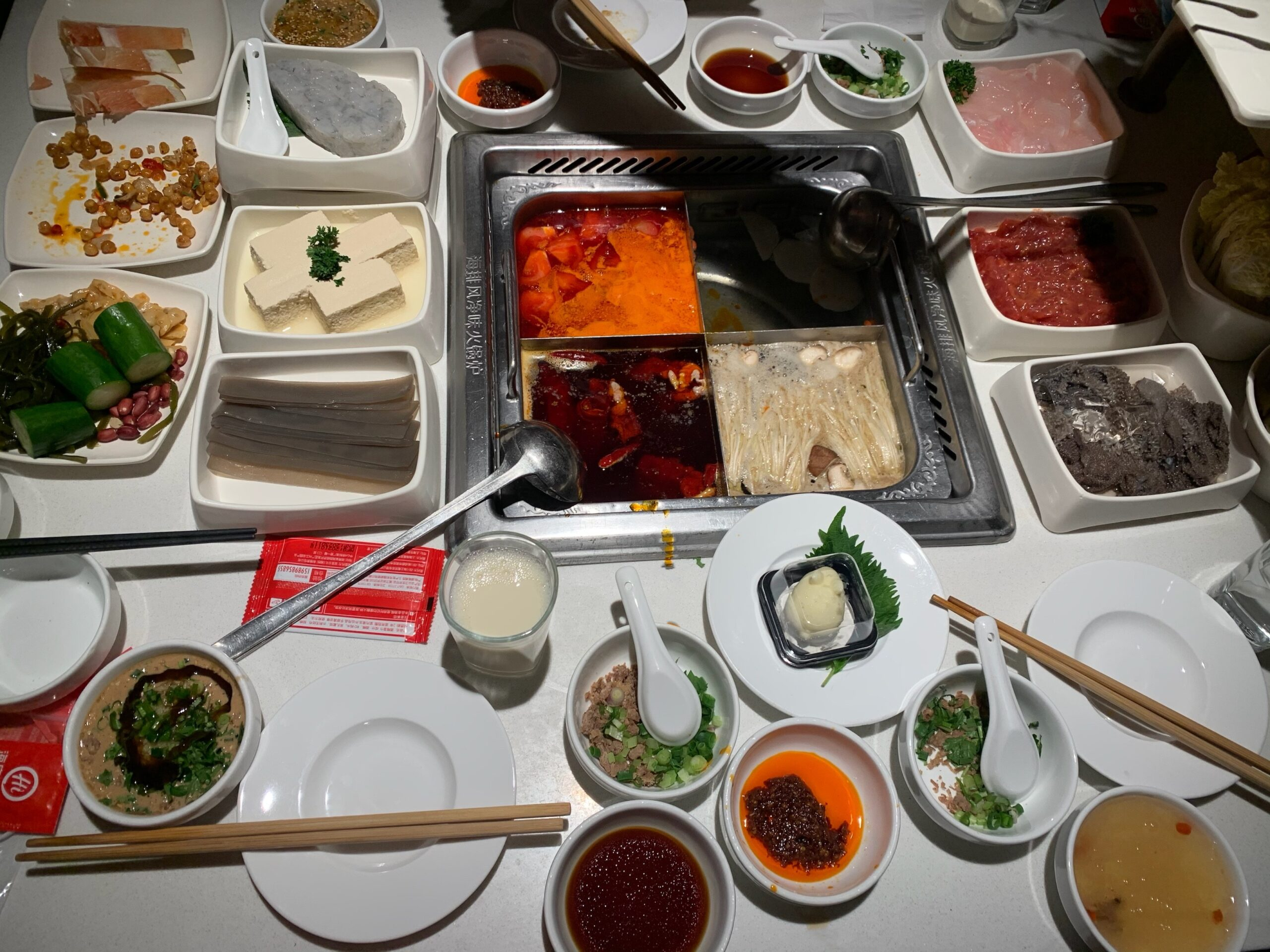 white table with several trays and plates of various foods
