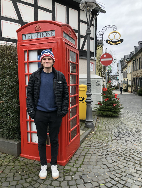 man stands in front of red telephone booth during daytime