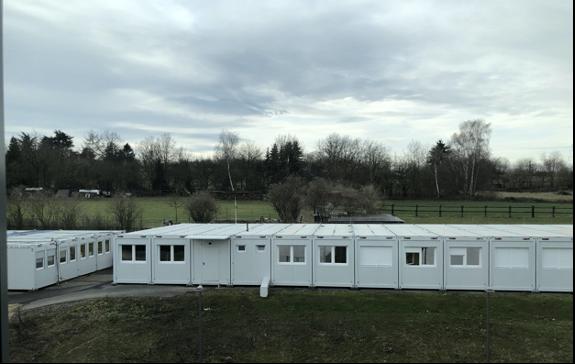 short white trailer buildings near trees during daytime