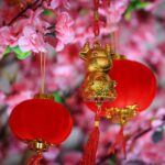 small golden ox decoration hangs near red and gold spherical decorations near pink flowers