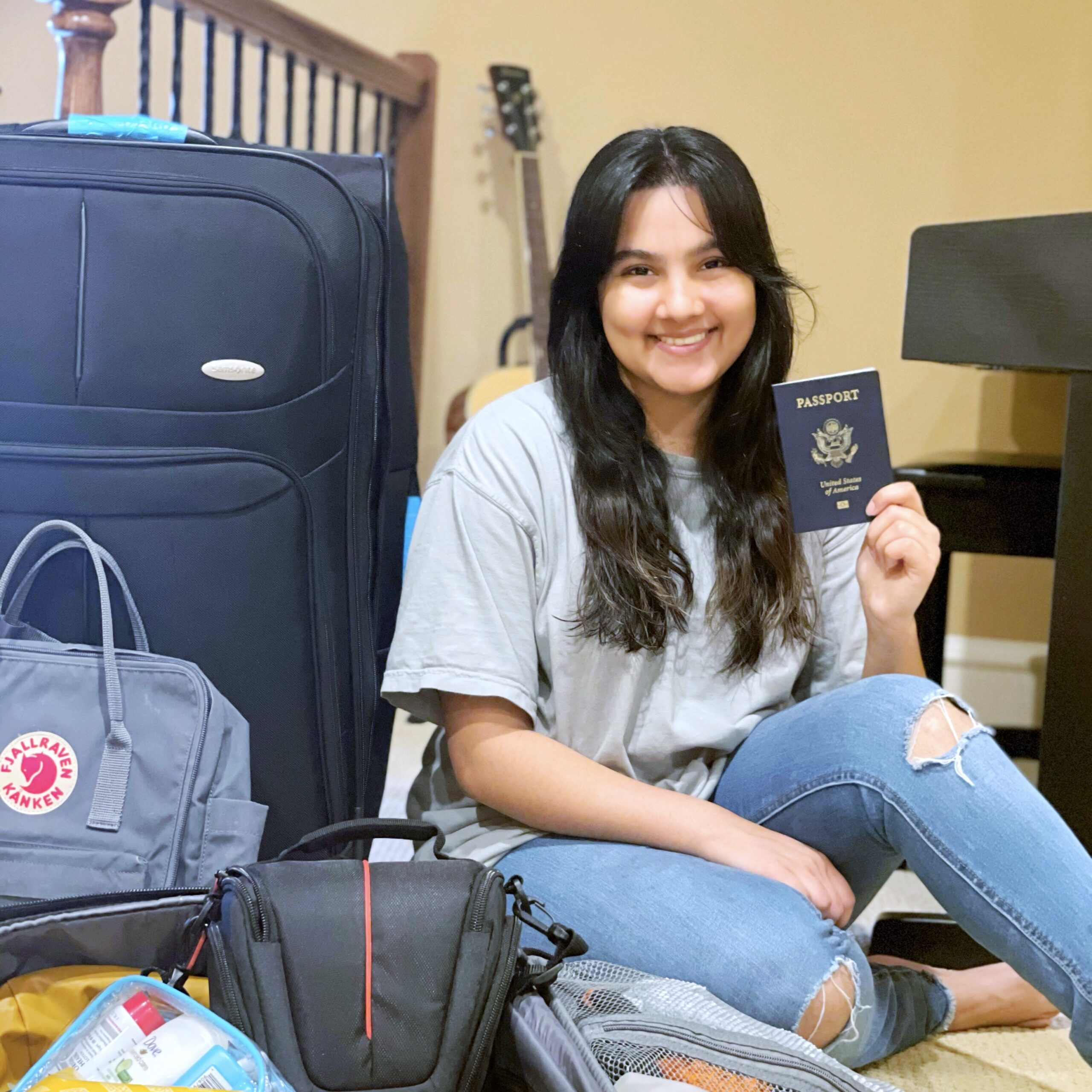 girl smiles holding up passport and sitting near many bags