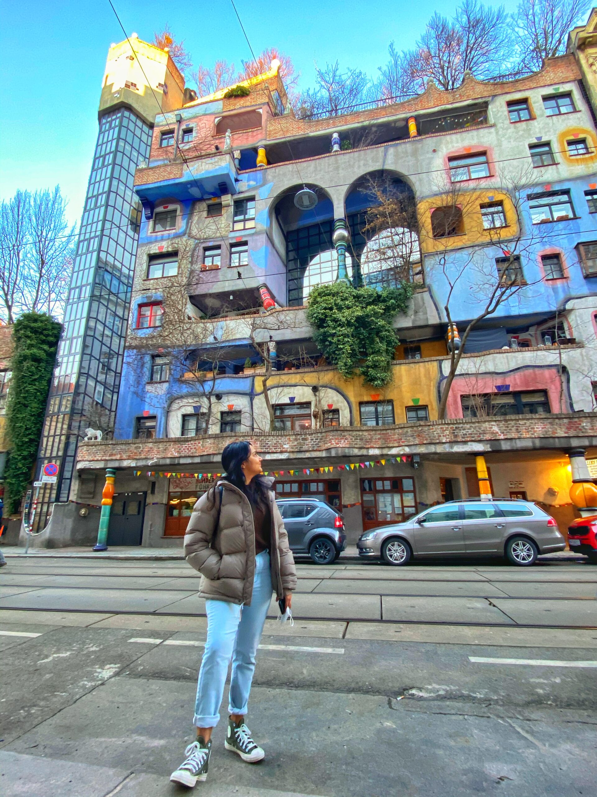 person stands in front of colourful buildings and street with cars during daytime