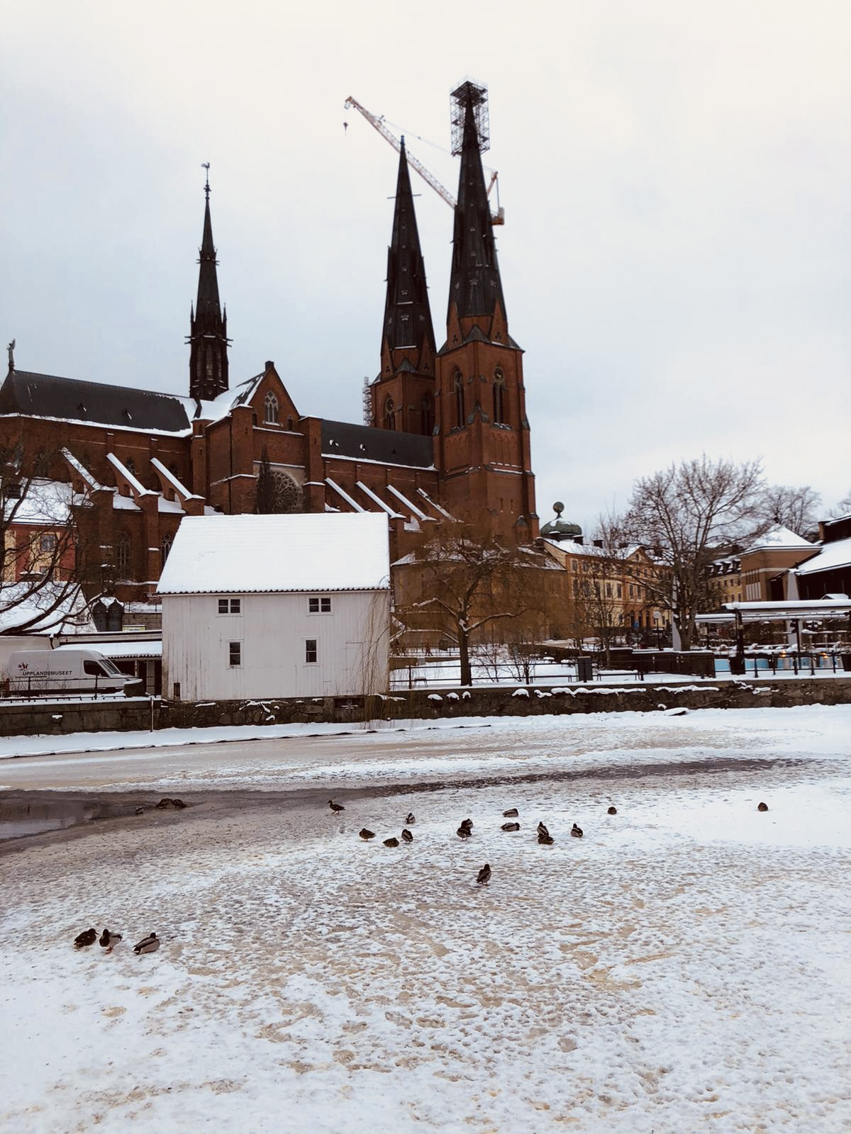 large historic building with spires near small white house in snowy city during daytime
