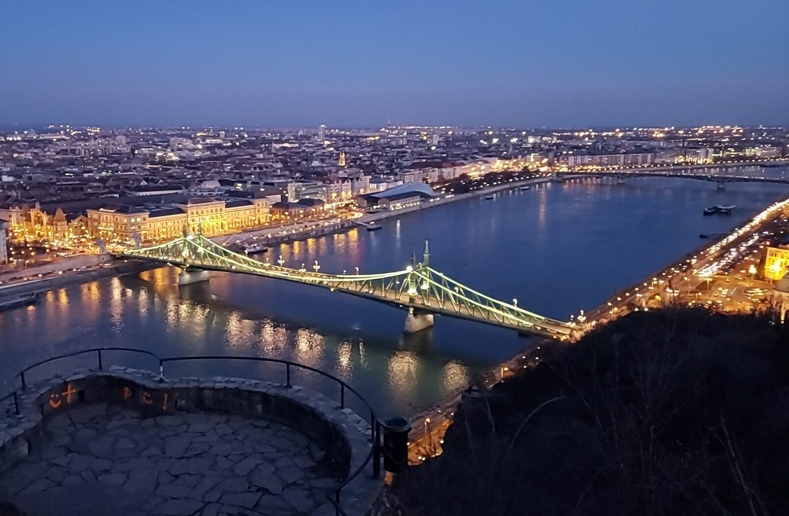 nighttime view of bridge, river and city