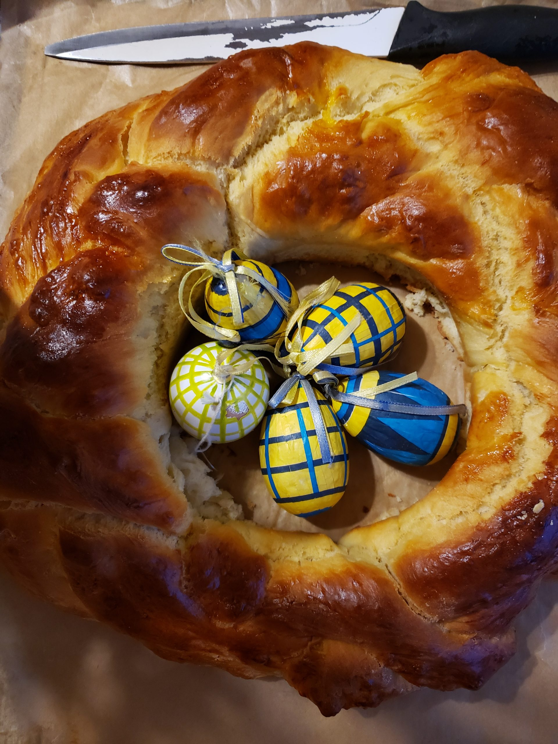 braided bread loaf with small colourful wrapped eggs on top