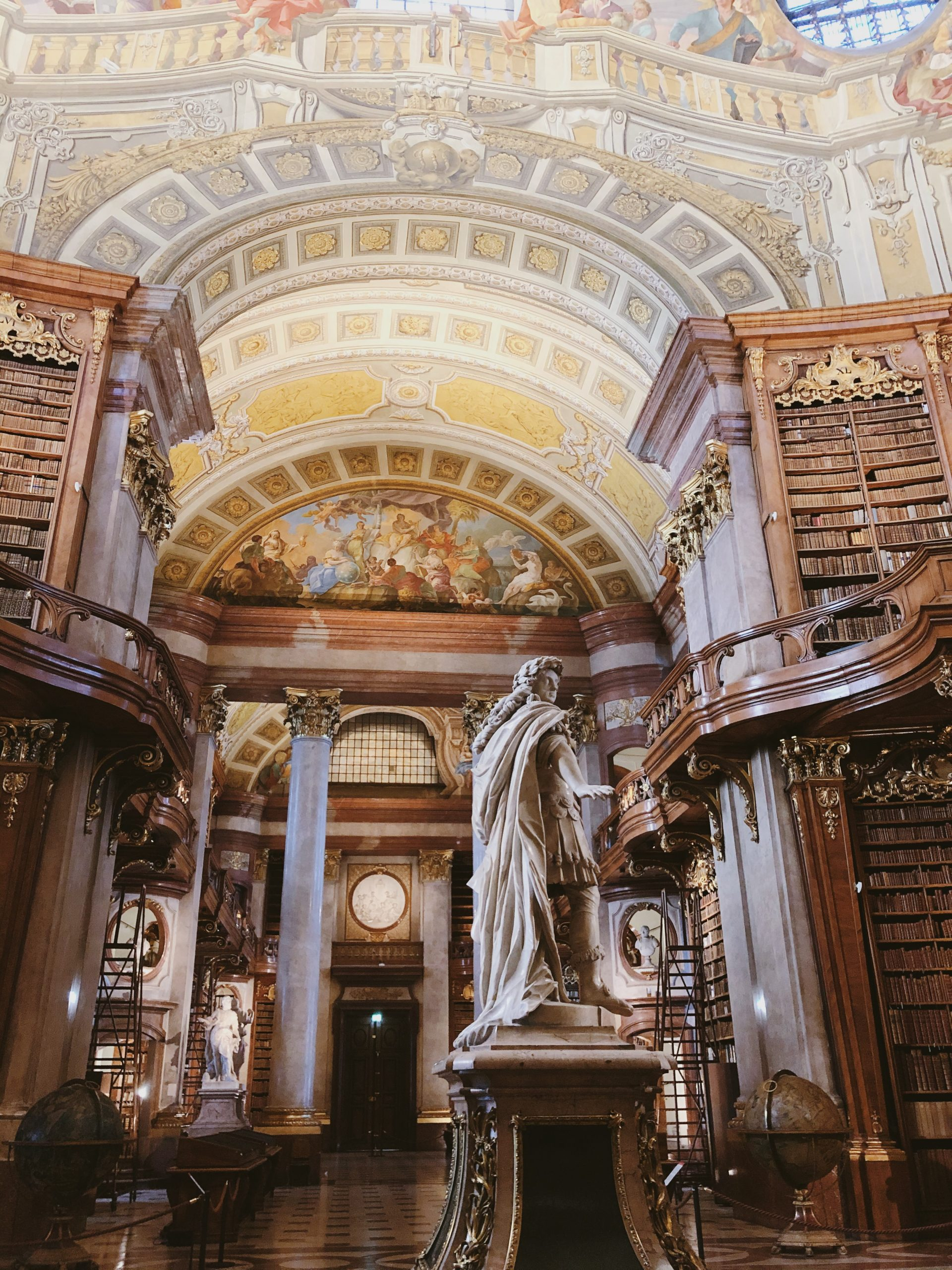 interior of historic library with domed ceilings and ornate pillars and sculptures