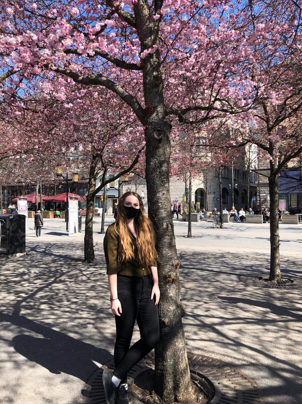 woman stands under flowering tree near buildings during daytime