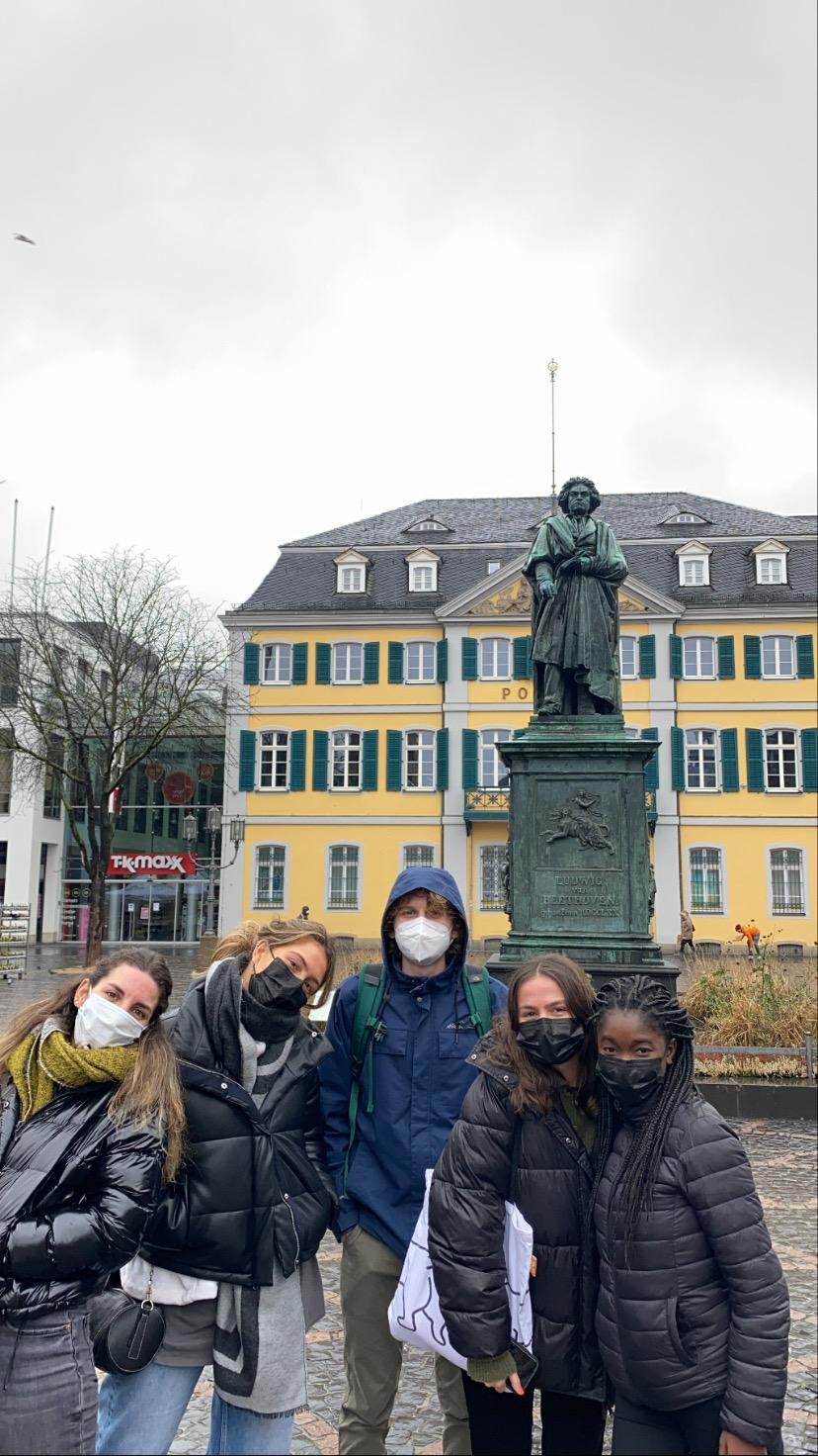 five people stand near statue, building and body of water while wearing face masks during daytime