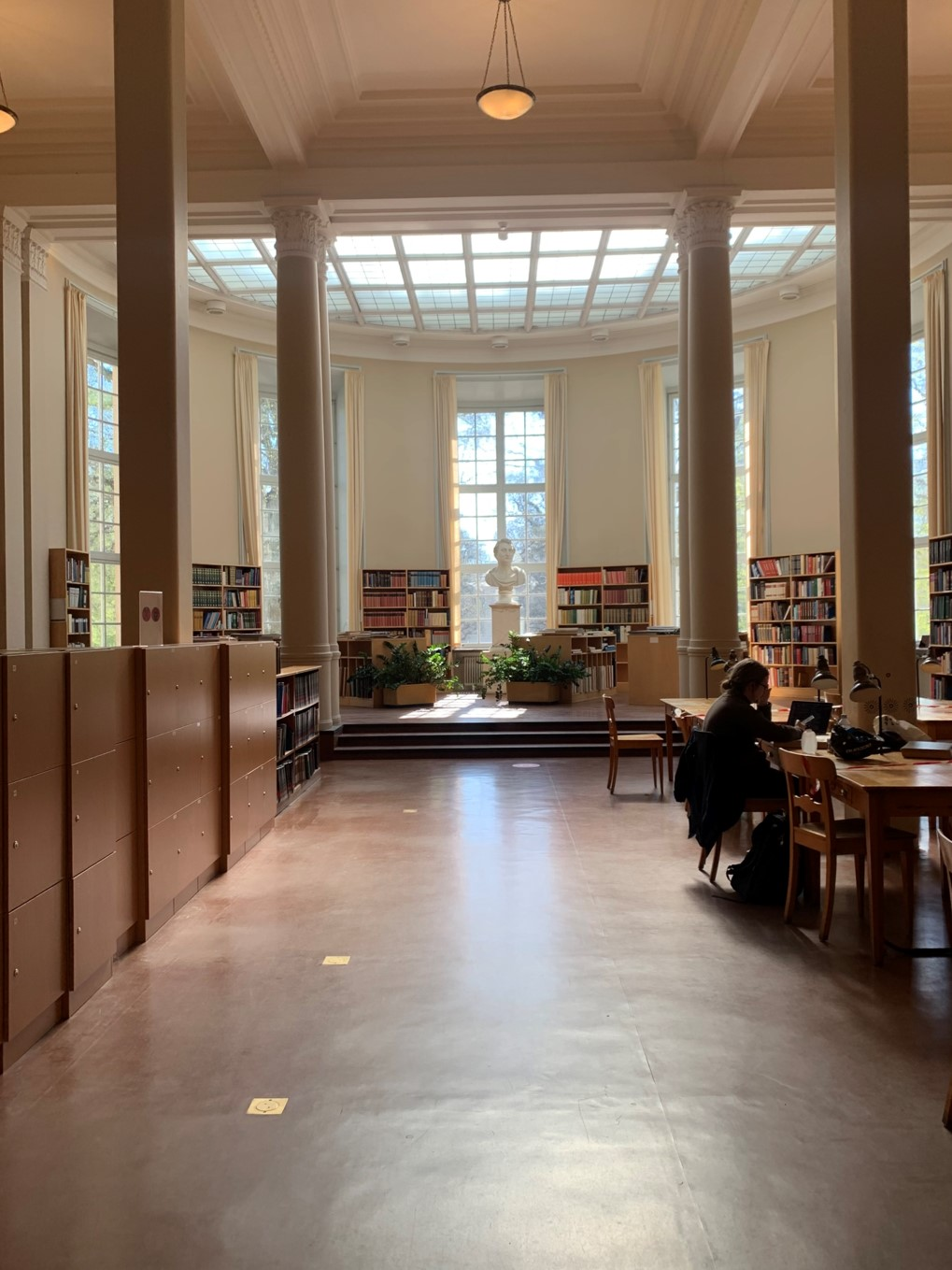 people studying inside of library with spacious corridor and skylight during daytime