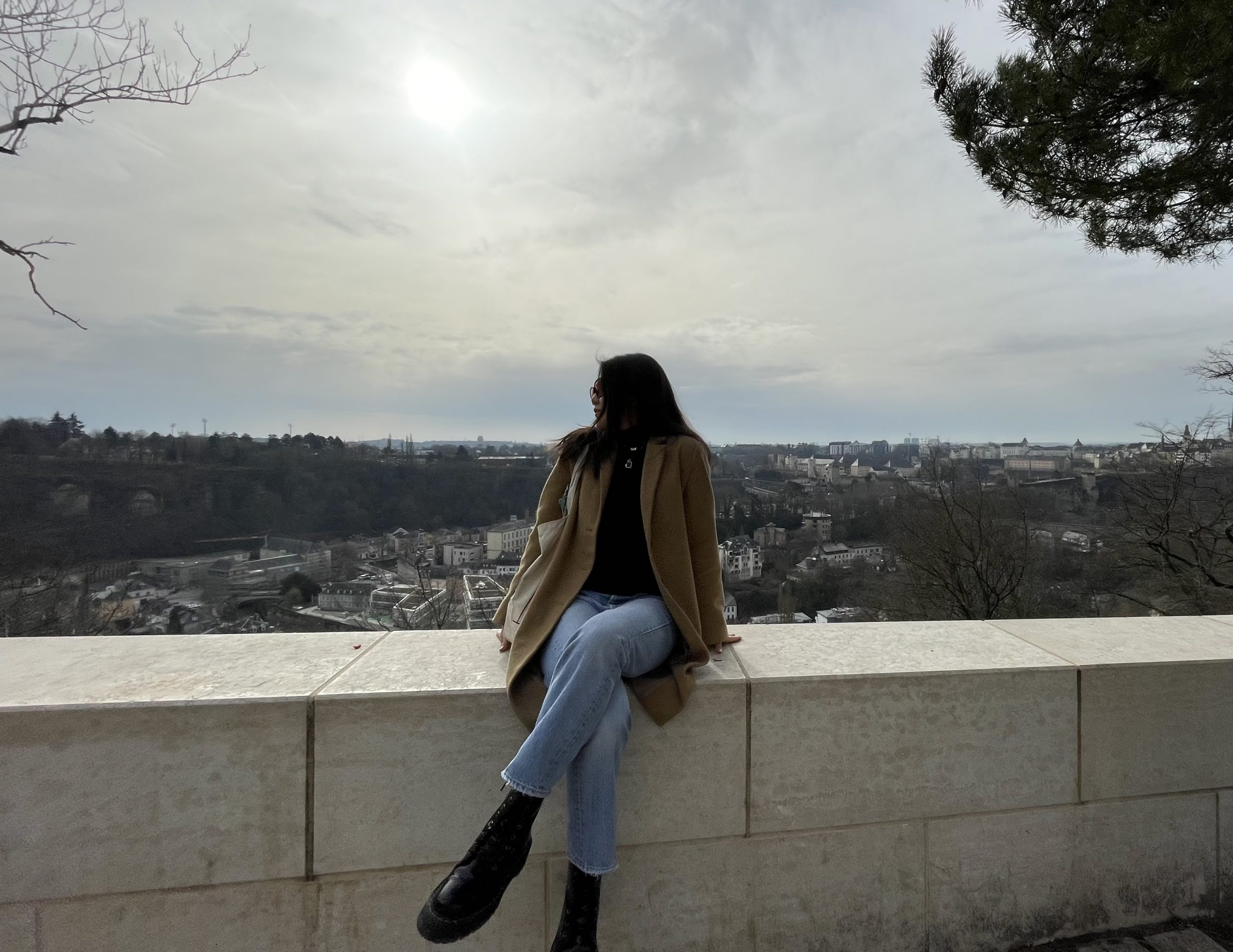 woman sits on wall overlooking city during daytime