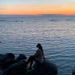 woman sits on rocks near large body of water during sunset