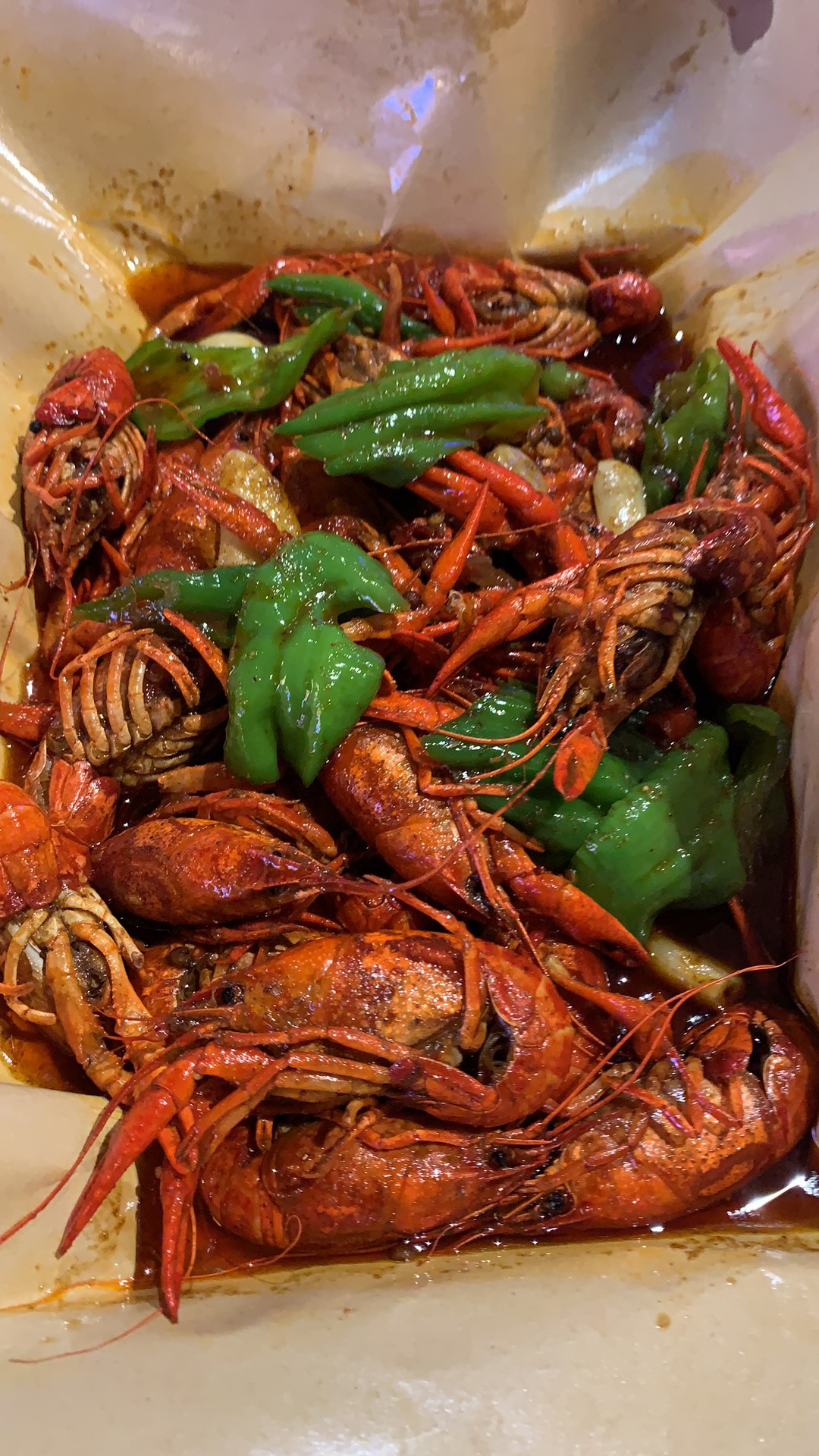 crayfish in red sauce with vegetables in plastic takeout container