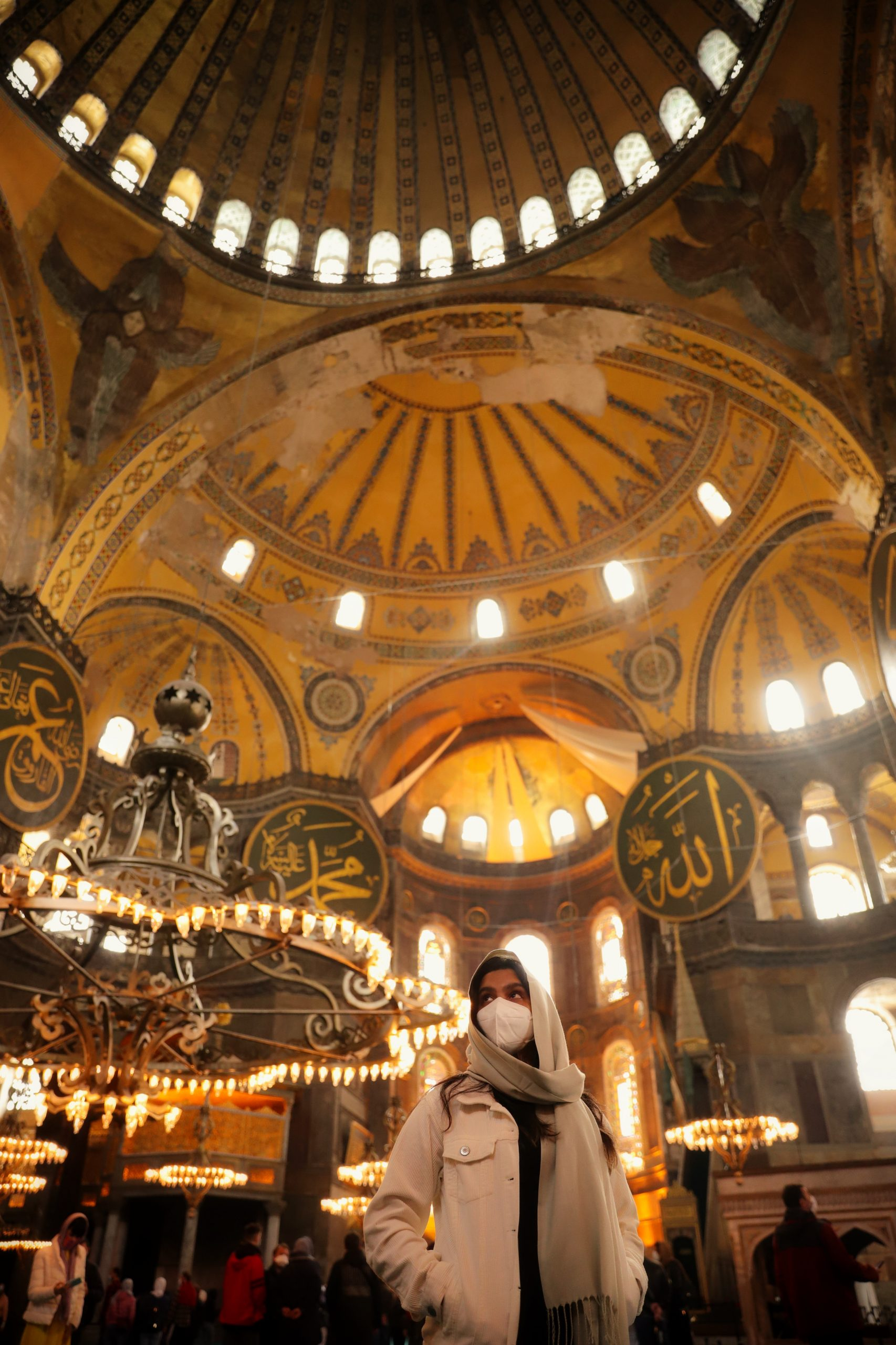 woman in mask poses in interior of domed building with intricate artwork