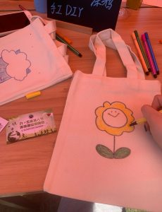 a person draws a flower on a white canvas bag