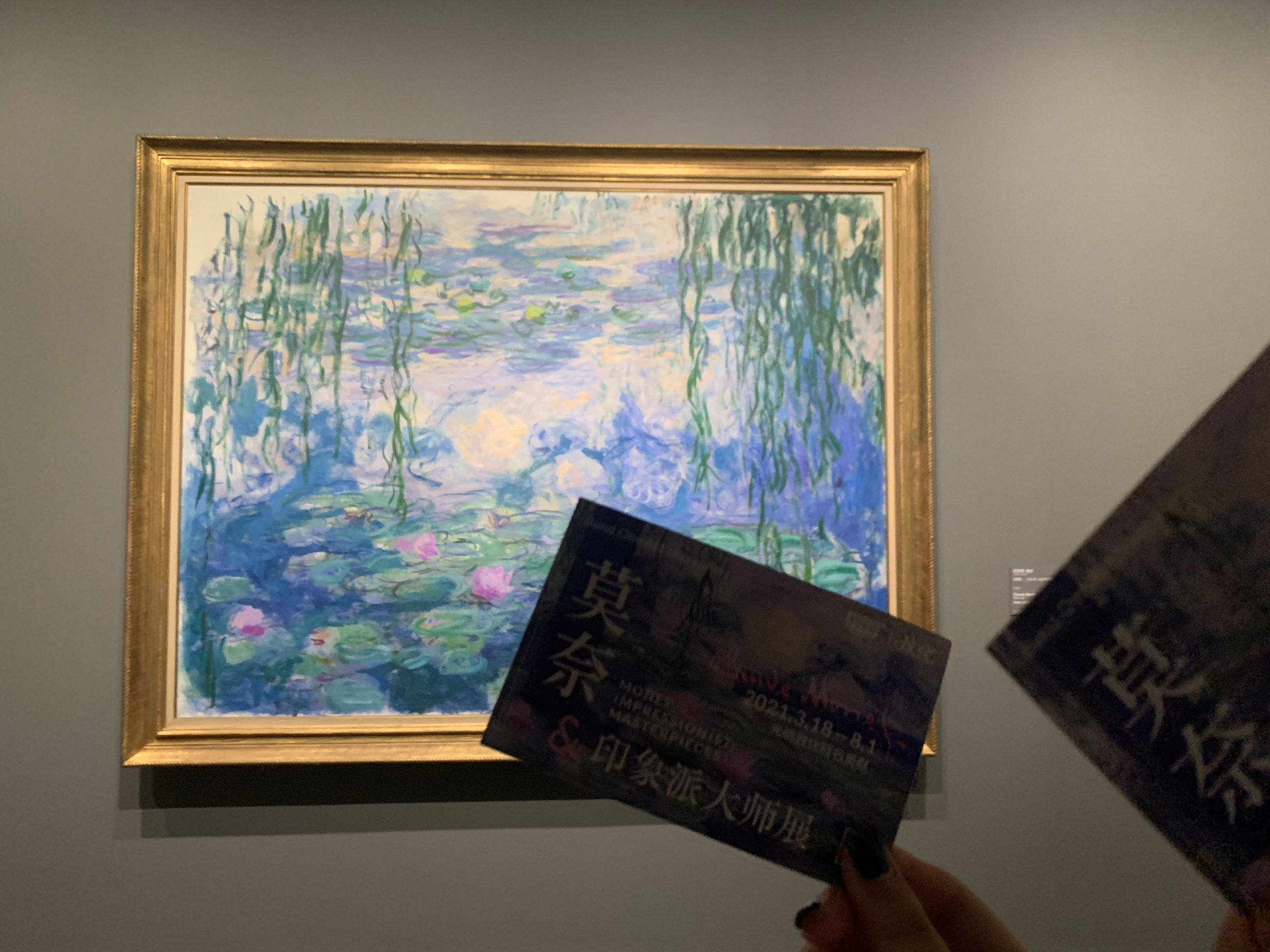 a monet painting on a wall with a person's hand in front of it