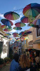 Rainbow umbrellas hang in the blue sky above a historic alleyway.