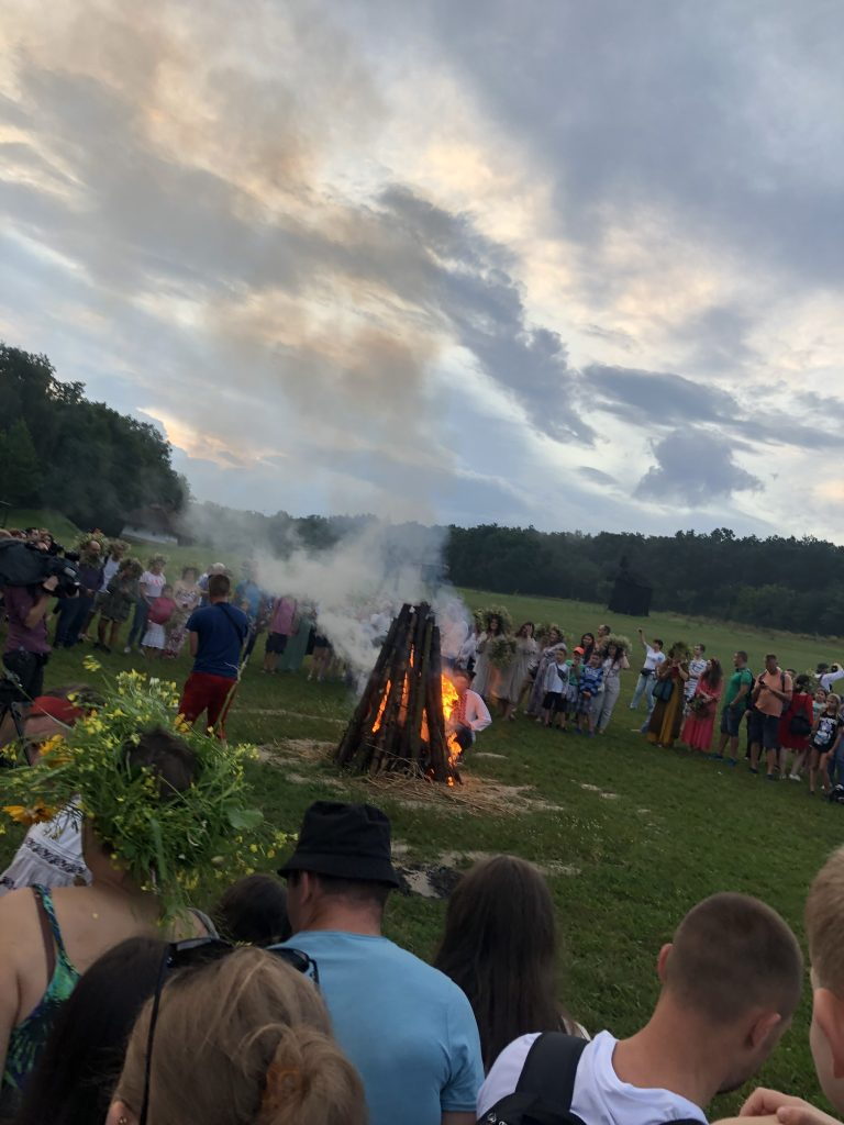 In an open field, people gather around bonfire preparations.