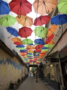 A village alley with colorful umbrellas hanging over-head.
