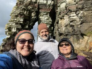 Downie smiles with her parents in front of the crags of Shetland.