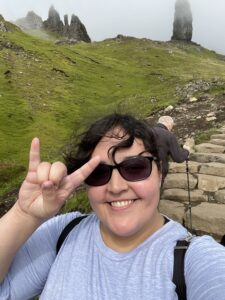 """Downie smiles and shows the """"hook 'em"""" hand sign while hiking to see the Old Man of Storr."""