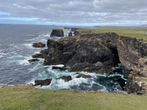 Waves crash into the rock and green grass of the Shetland Coast.